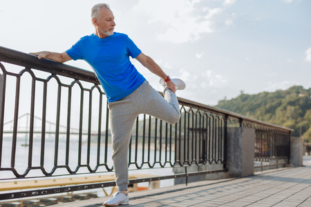 Senior man stretching leg muscles before morning run