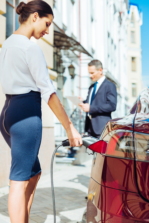 Attractive skillful businesswoman refilling the car