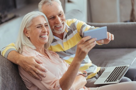 family sofa: Delighted smiling aged couple making selfies at home