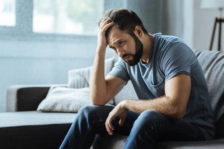 Trauriger düsterer Mann , der seine Stirn hält Standard-Bild
