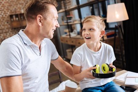 Opgewekte jongen die zijn vader voor nieuwe hoofdtelefoons dankt Stockfoto