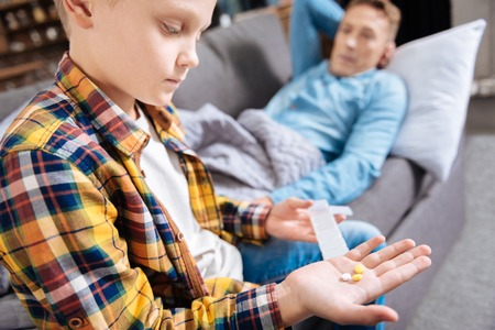 Pre-teen boy holding pills for his ill father