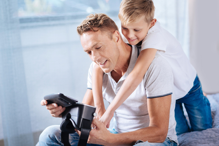 he: Affectionate son cuddling his father while he setting VR headset