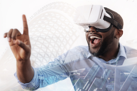 Excited young man wearing virtual device Stock Photo