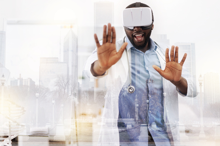 Cheerful doctor using virtual reality mask Stock Photo