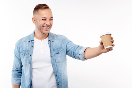 Cheerful young man giving a paper cup of coffee