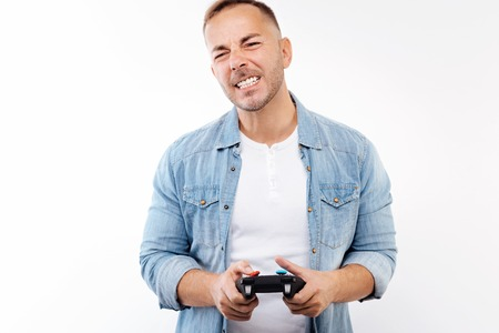 Young man grimacing after losing in video game