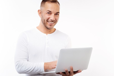 Pleasant man posing on white background with laptop