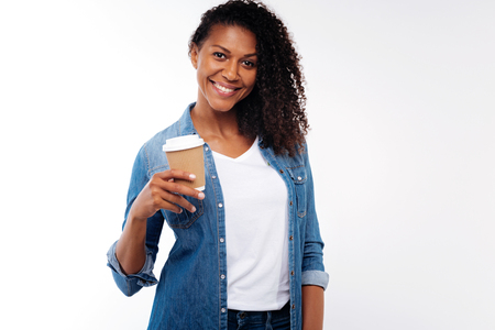 Curly young woman posing with a cup of coffee