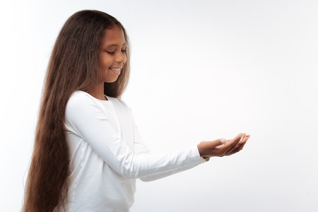 Beautiful pre-teen girl holding something small in her hands