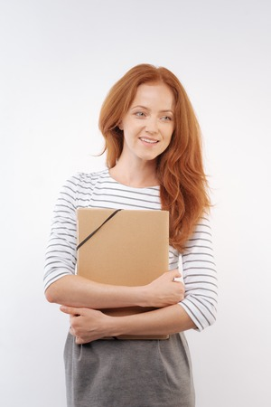 Red-haired woman pressing folder to the chest