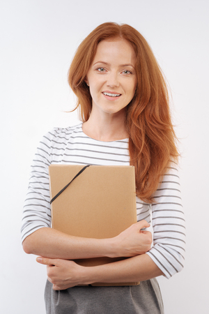 Young red-haired woman posing with folder in hands Stock Photo
