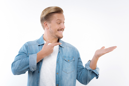 Upbeat man pointing at imaginary object in his hand
