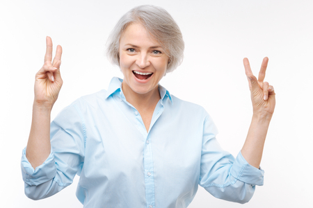 Cheerful grey-haired woman showing v signs with both hands