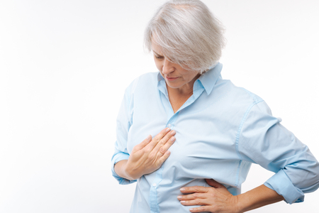 Grey-haired woman suffering from stomachache Stock Photo