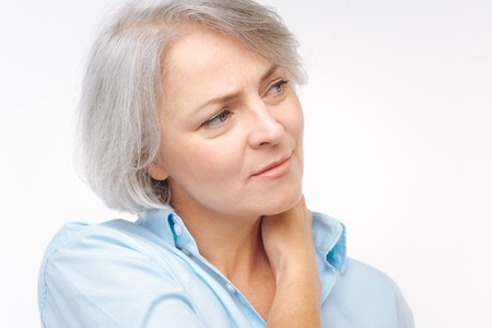 Close up of grey-haired woman suffering from neck pain