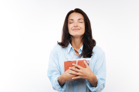 Happy young woman pressing gift box to her chest Stok Fotoğraf