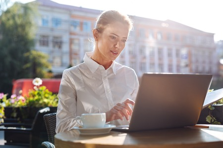 Beautiful businesswoman typing on laptop in cafe Stock Photo
