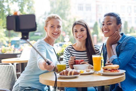Charming women taking selfies with monopod in cafe Stock Photo