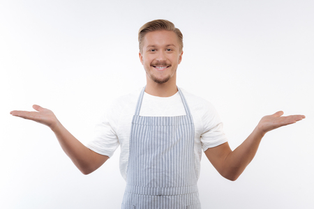 Cheerful man in apron spreading hands in welcoming gesture Imagens - 86903875