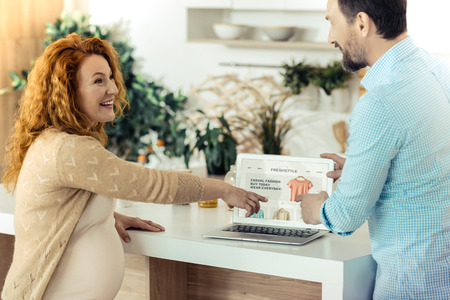Amused pregnant woman pointing at the monitor Stock Photo