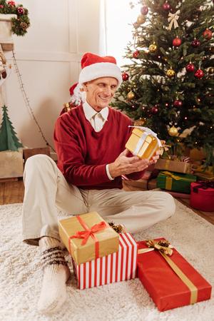 Happy elderly man opening presents