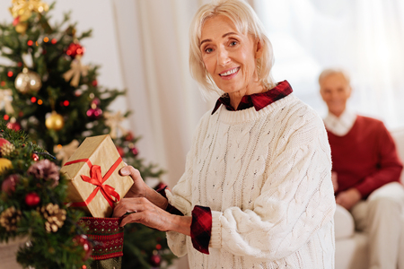 Attractive female person putting present into stocking