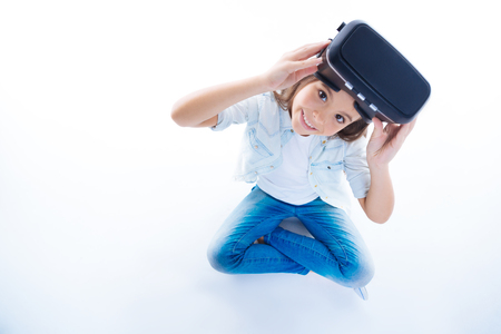 Top view of a happy cheerful girl holding virtual reality glasses isolated in white.