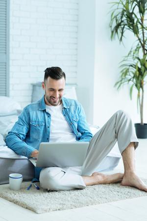 Smiling millennial freelancer enjoying working at home