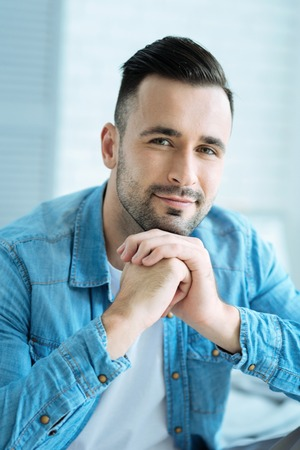 Relaxed millennial guy looking into camera and smiling