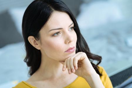 Pensive brunette girl thinking over something