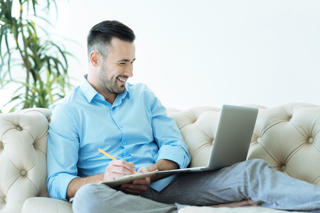 Positive minded businessman taking notes and smiling Stock Photo
