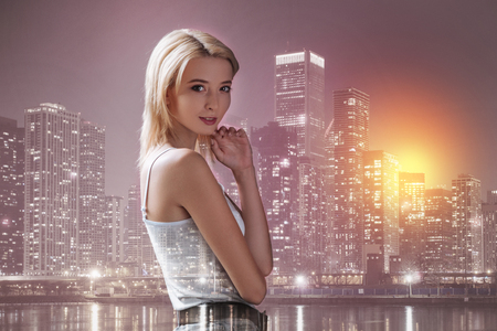 Adorable girl smiling at you against city lights Stock Photo