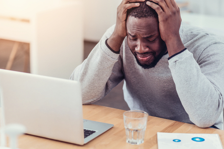 hysteria: Stressed African American guy crying at work