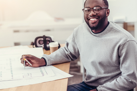 Beaming engineer in pullover and glasses looking into camera