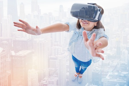 Collage of little girl in VR headset standing atop urban landscape
