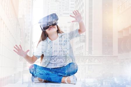 Little girl testing her new VR headset while squatting cross-legged