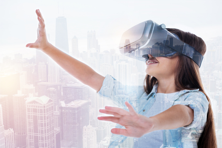 double game: Smiling girl in VR headset reaching to the sky Stock Photo