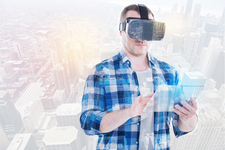 double game: Young man using tablet while wearing VR headset Stock Photo