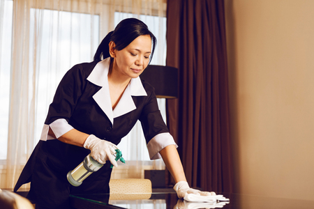 Attentive room cleaner polishing glass table