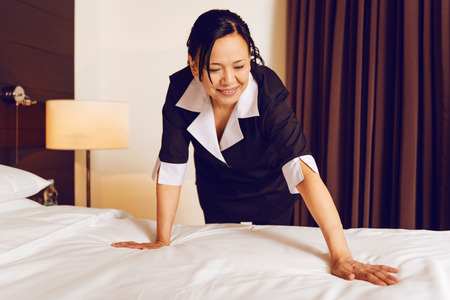 Attentive foreign hotel staff making bed Stock Photo
