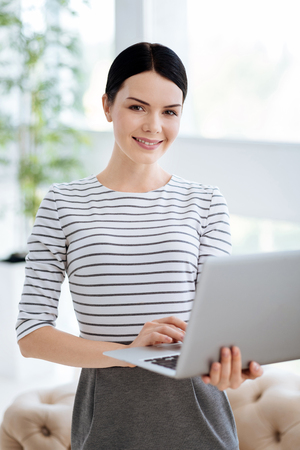 Happy smart woman standing in her office