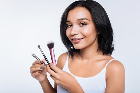 Dark-haired young woman holding makeup brushes
