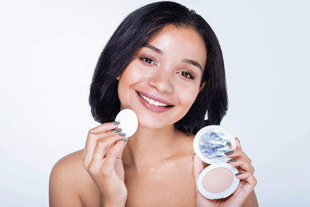 Pretty young woman showing her powder with a puff
