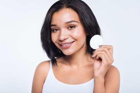 Pleasant smiling young woman holding a cotton pad