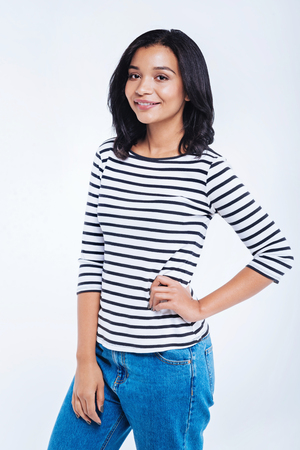 Charming woman in striped pullover posing against white background