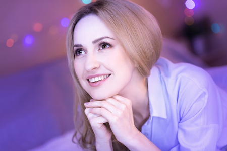 Inspired smiling young lady dreaming Stock Photo