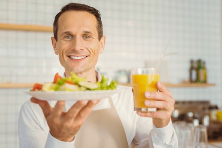 Cheerful happy cook man holding his breakfast