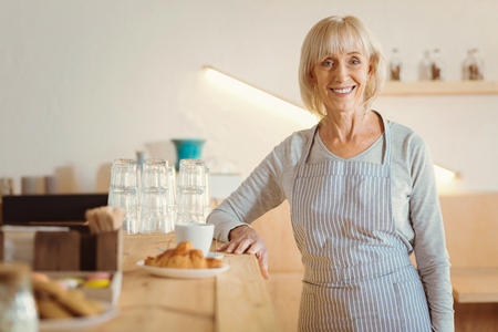 Happy elderly woman looking at you