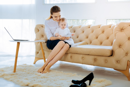 Elegant busy mother sitting with her child Stock Photo